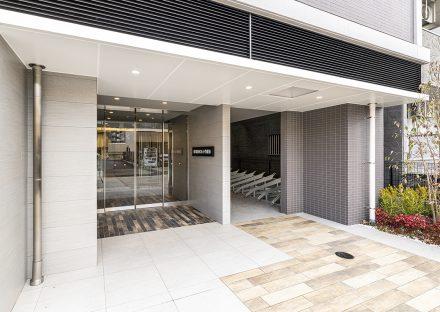 愛知県小牧市のレトロとモダンを組み合わせたデザインの賃貸マンションの色鮮やかな植栽があり、モダンなエントランス