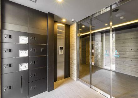 名古屋市中川区の賃貸マンションのダークカラー宅配ボックスのある風除室