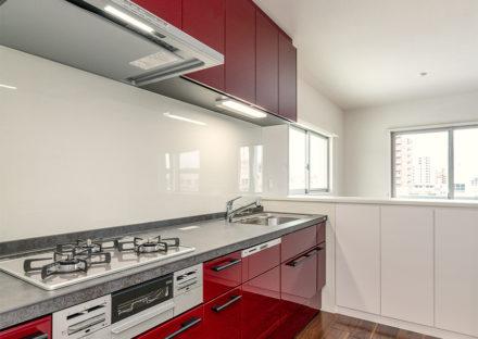 名古屋市天白区の賃貸マンション併用住宅の吊戸棚の付いた赤色のガスコンロ付きキッチン