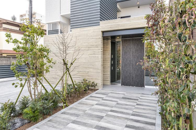 名古屋市中川区の賃貸マンションの両側に植栽のあるエントランス