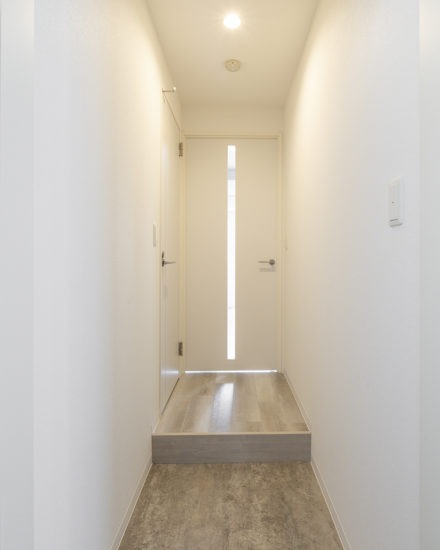 名古屋市中区のおしゃれなワンルームマンションのスリットから光が入る明るい玄関