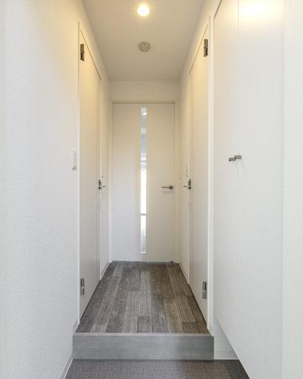 名古屋市中区のおしゃれなワンルームマンションのダークの色合いの床と、白の壁のコントラストがキレイな玄関