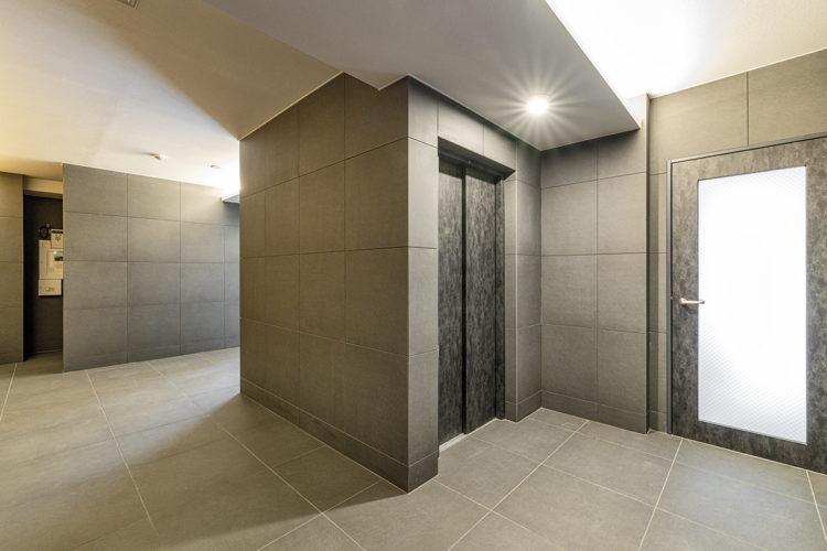 名古屋市中区のおしゃれなワンルームマンションの大判タイルの高級感あるエレベーターホール