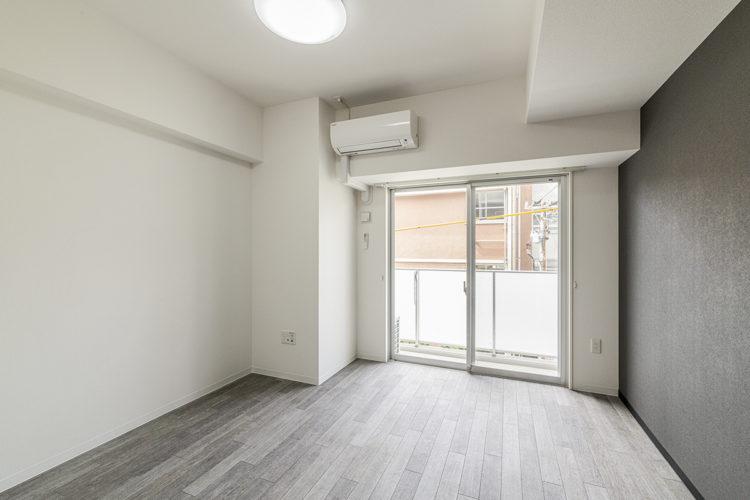 名古屋市中区のおしゃれなワンルームマンションのエアコンの付いた落ち着いた色づかいの洋室