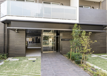 名古屋市中区のおしゃれなワンルームマンションの両サイドに緑があるエントランス