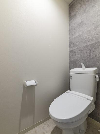 名古屋市名東区のモダンデザインの壁があるトイレ