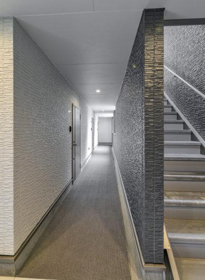名古屋市名東区の凹凸のあるモダン壁の1階共用廊下
