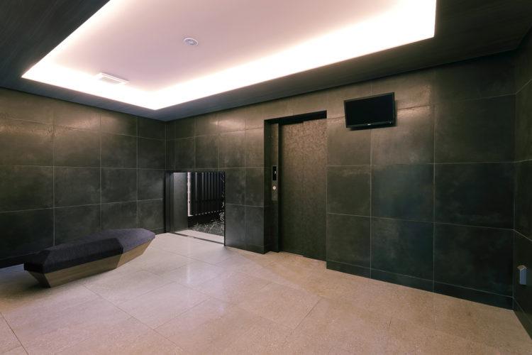 名古屋市千種区の13階建て賃貸マンションの大判パネルの高級感あるエレベーターホールとおしゃれな椅子