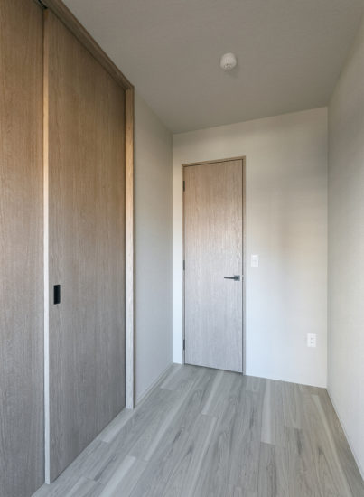 名古屋市千種区の13階建て賃貸マンションの木目のドアの付いたシンプルな洋室