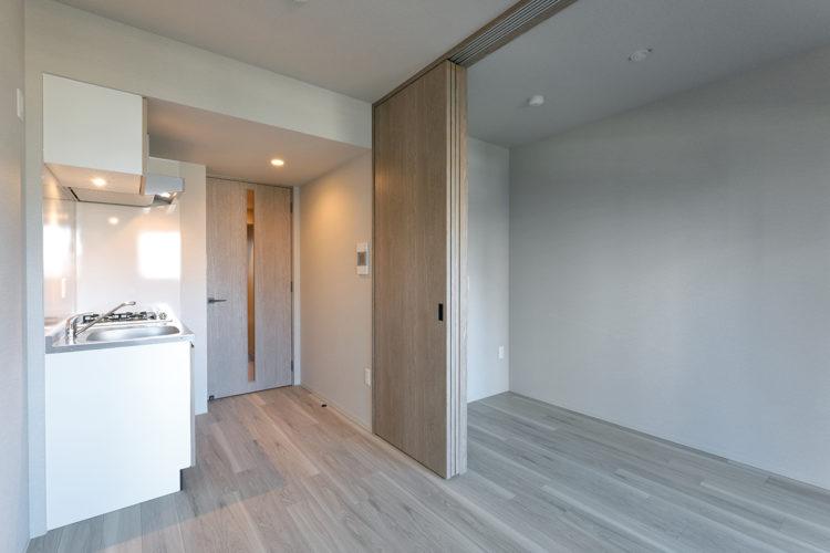 名古屋市千種区の13階建て賃貸マンションのコンパクトなキッチンと洋室